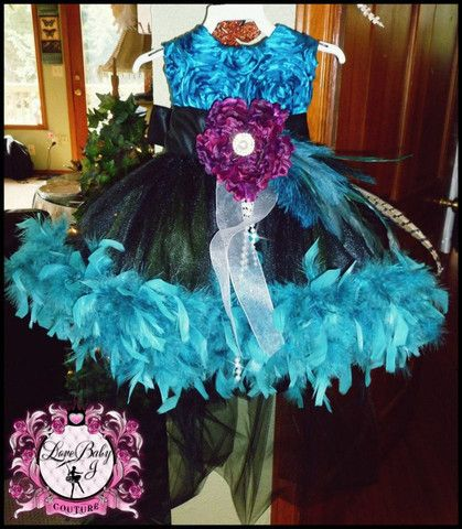 A Tutu Dress For The Not So Ordinary Girl !This absolutely stunning tutu dress is made in yummy hues of midnight black, teal, and purple. The bodice features a beautiful satin rosette material.There is a removeable brooch at the waistline overflowing with hand selected silken blossoms, fabulous chandelle feathers, turkey feathers, peacock feather, and luxurious strings of pearls. The waistline also features a gorgeous satin sash with large bow in the back. $200 #wedding #birthday #dress…