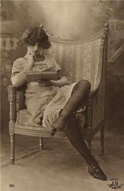 Unknown woman reads in this image from a 1920s French postcard.