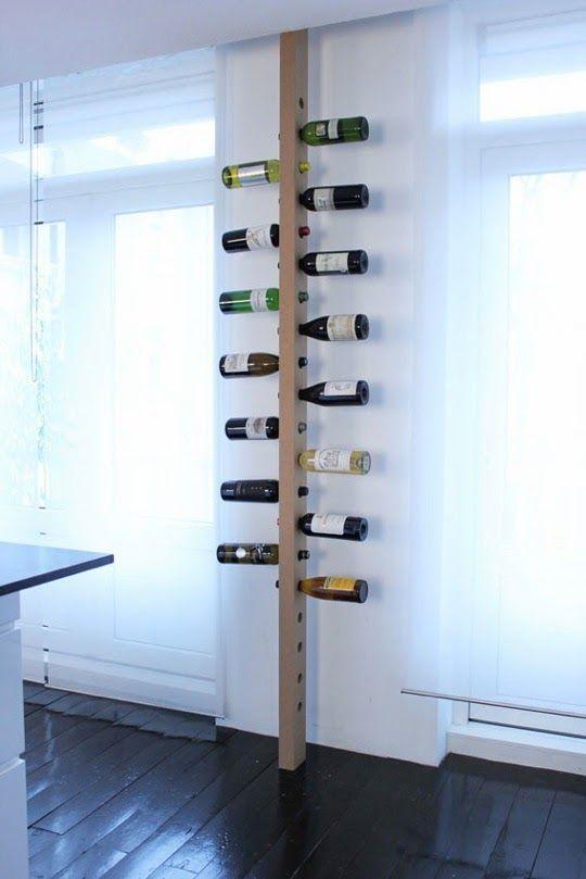 Um pilar que é uma garrafeira vertical, com as garrafas bem à vista ...