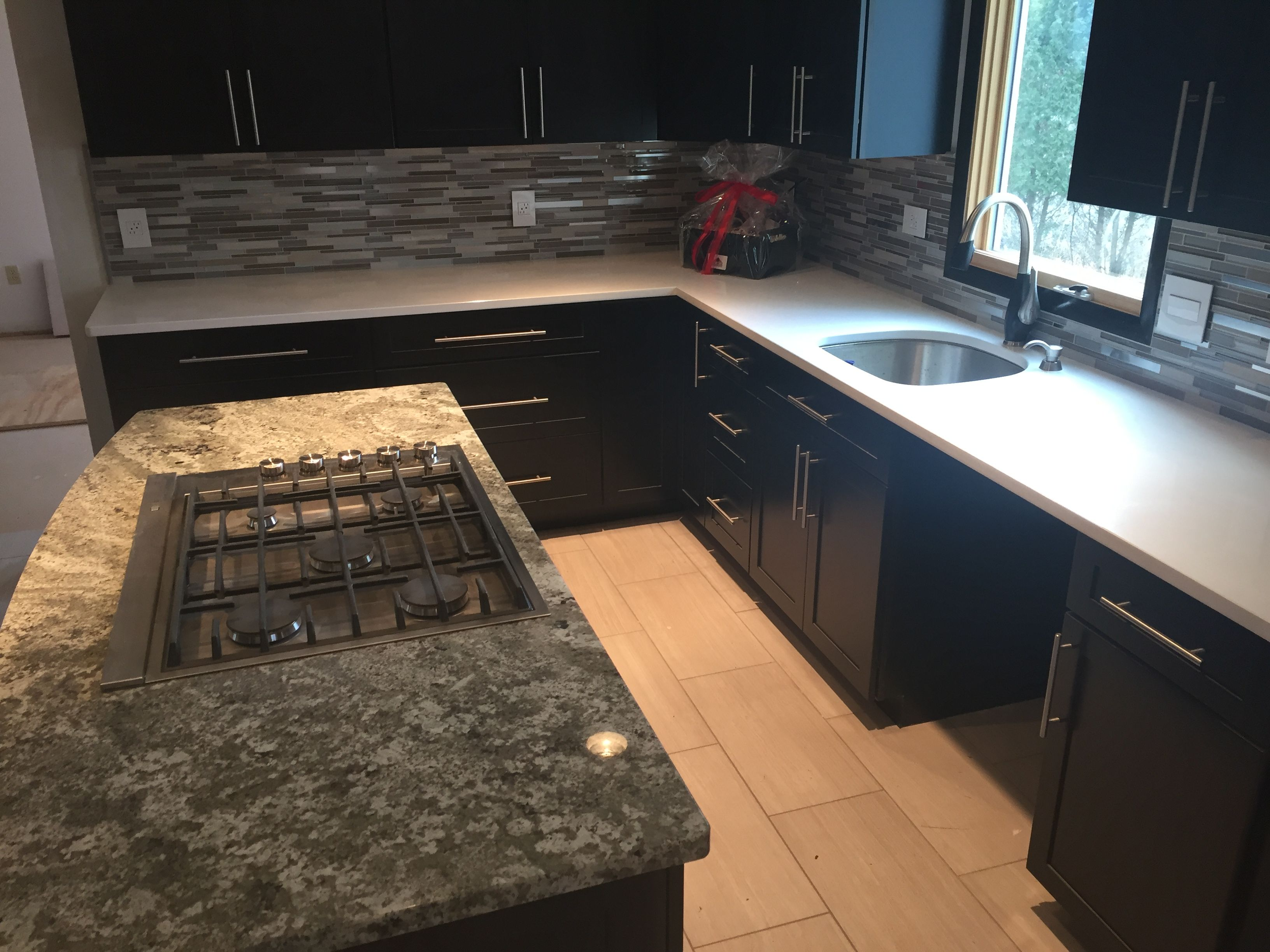 We installed Ebony kitchen cabinets with glass mosaic tile ...