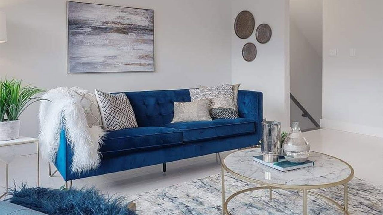 Blue velvet sofa with round glass coffee table gold