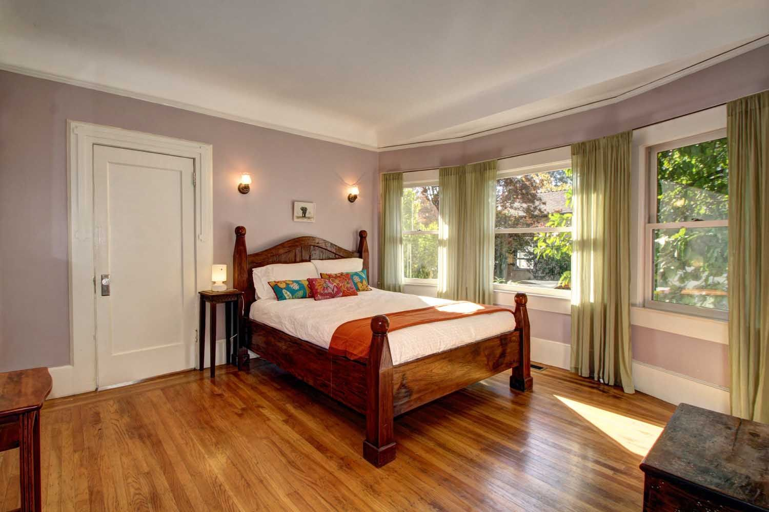 First-floor bedroom in this 1915 Craftsman boasts hardwood floors, detailed carving and lots of windows. #HomesEastSacramento