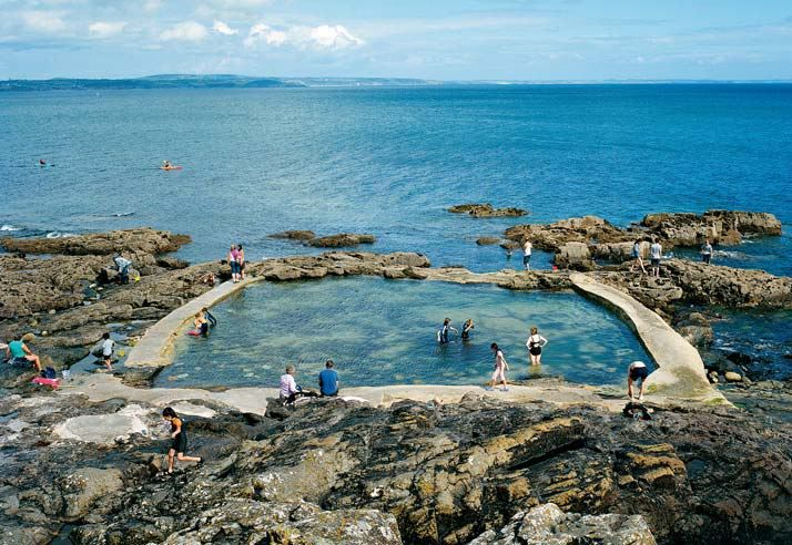 """United Kingdom—A """"sea pool"""" constructed along a stretch of rocky coast invites refreshing dips in the Cornish village of Mousehole. Such pools, filled by seawater at high tide, were popular in the U.K. during the 1930s. Today some 30 of them remain in use."""