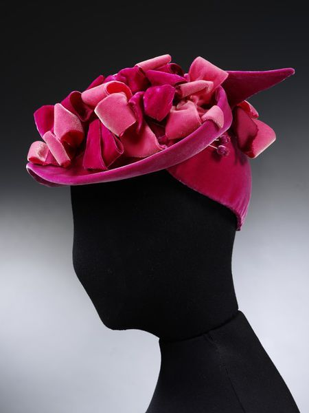 Hat and hat pins   Aage Thaarup (Danish-born, 1906-1987)   Made in London, 1950's   Material: velvet   Hats were considered an essential fashion accessory in the 1950s. The two main styles during this time were small skull-caps, or wide 'saucer' hats. A hat such as this would be suitable for a cocktail party or dinner   Aage Thaarup moved to London in the 1930's. He was one of the most successful milliners of his age, and also designed for the Queen   VA Museum, London