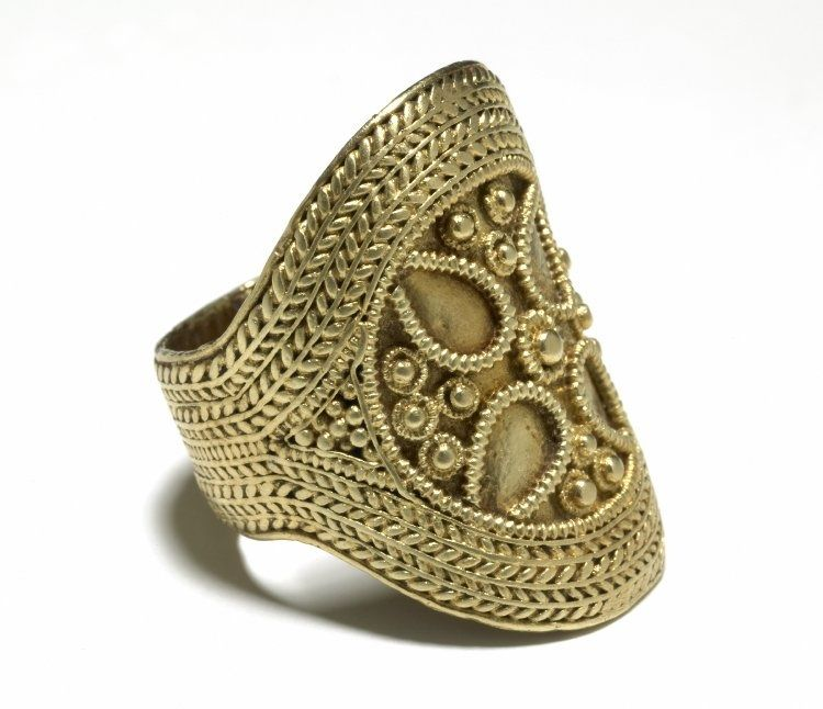 Anglo-Saxon Finger Ring, 7thC - 8thC AD. Gold finger-ring; broad, flat hoop expanding to large oval bezel; covered with bands of twisted wire, simulating plaiting and diverging at the shoulders to enclose a circular design in pearled wire and pellets. Principal motive may be a quatrefoil, pellets in centre and interspaces forming a cross pattee. | ↳THE BRITISH MUSEUM