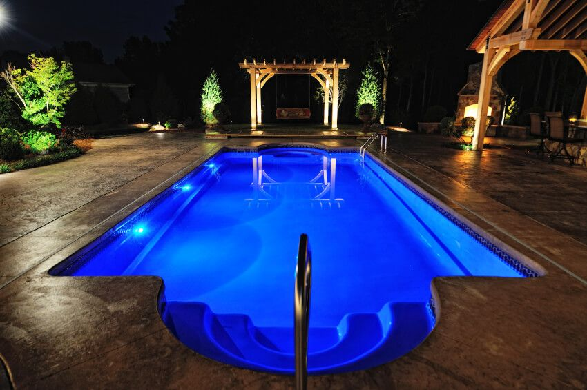 This traditionally shaped pool glows with a deep blue at night, surrounded by a rich patio with full outdoor fireplace, bench swing, and sheltered dining area.