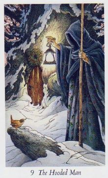 The Hooded Man (The Hermit)  - Wildwood Tarot - A hooded figure carrying a lantern and a walking stick and wearing a robe decked with holly, confers with a wren in the foreground, outside a wreath-hung door into the World Tree.