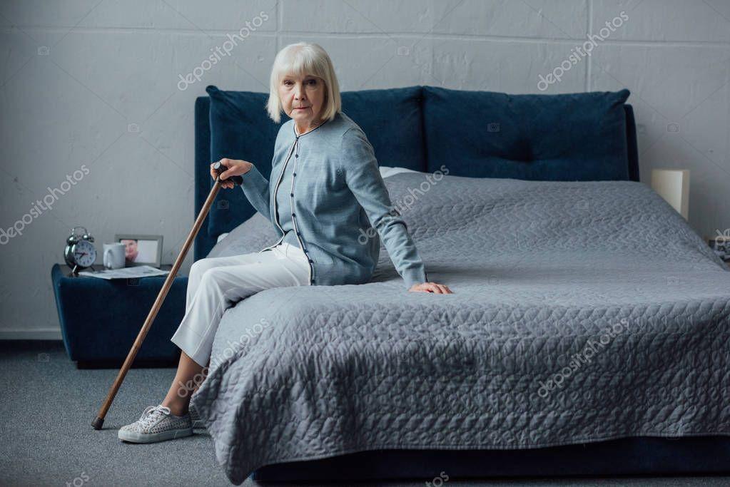 Senior Woman Sitting Bed Walking Stick Home Looking Camera Stock