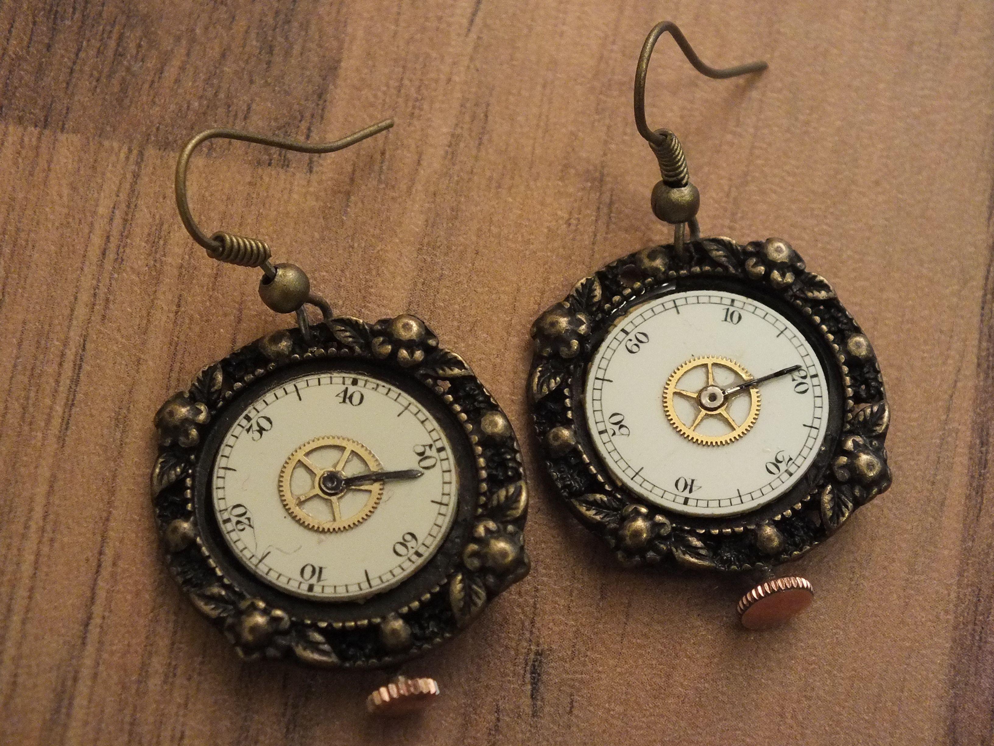 Pair of clock face earrings on a brace base.  Ein Paar Zifferenblattohrringe auf einem Messinguntergrund.
