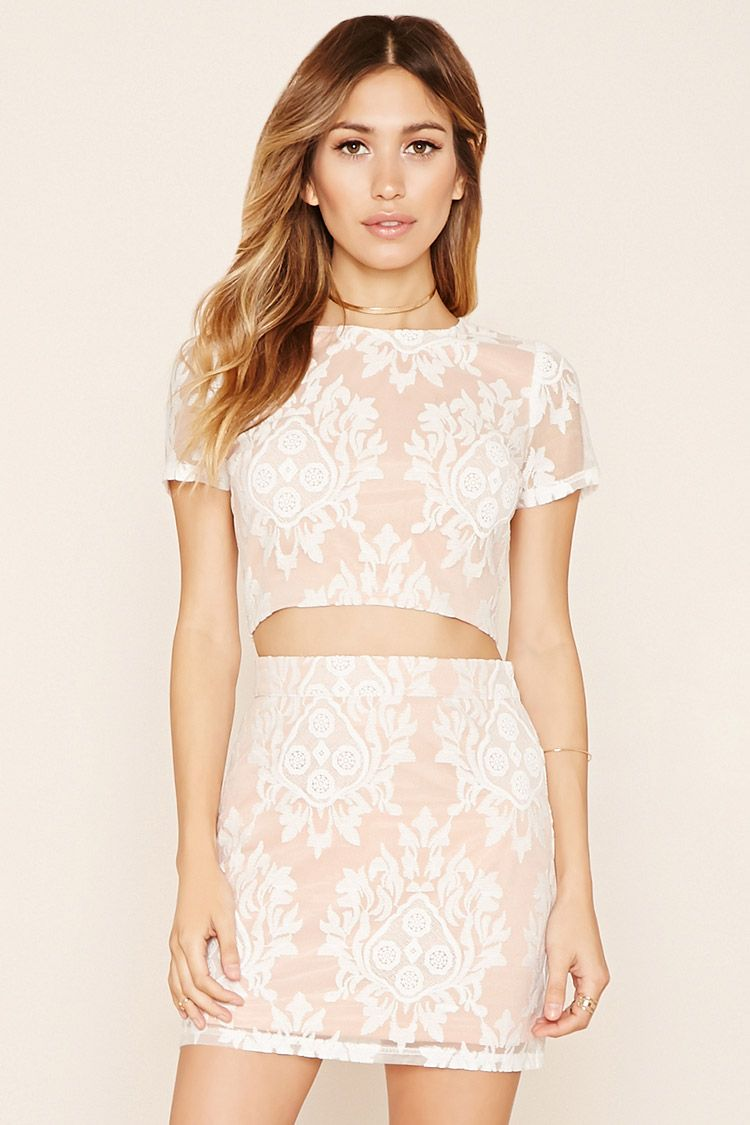 c59e6c33c08 A crop top featuring embroidered lace, short sleeves, a round neckline, and  an exposed back zipper.