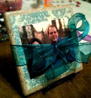 Buy a rough surfaced tile from Lowe's (less than a dollar) and mod podge pretty scrapbook paper on it. Then mod podge picture over that. Let dry and wrap with a pretty bow. Easy and cheap! You can also include a small stand to set the tile on. - Cute!