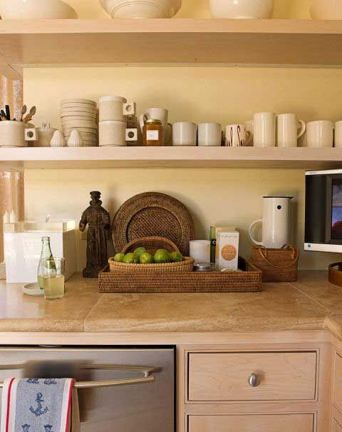 """CONTAIN KITCHEN CLUTTER WITH TRAYS """"Baskets and trays are very homey and useful, not just for carrying things but also to organize collections,"""" says designer Patrick Wade about his 60 square-foot kitchen. Light-colored wood and walls also make it feel more spacious. JOSÉ PICAYO."""