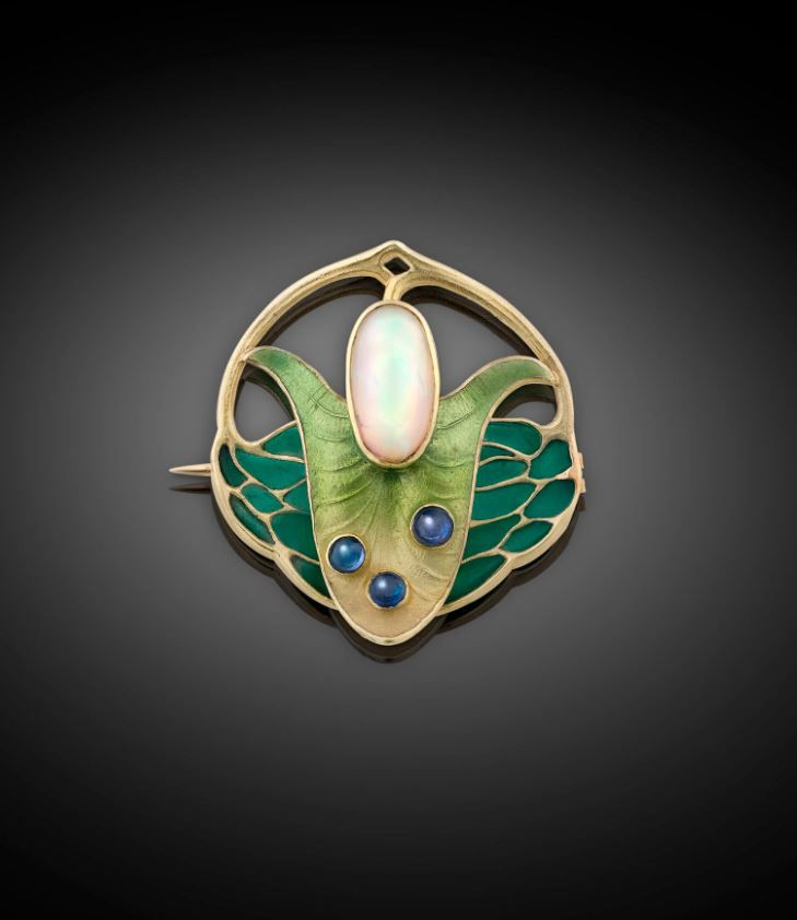 A beautiful white opal cabochon is surrounded by vivid enamel in this outstanding Art Nouveau brooch by Thodor Fahrner of Germany. A leader in magnificent Art Nouveau jewelry creation, this pin takes the form of a flower, with the opal serving as the center, highlighted by beautiful green enamels and three blue sapphire cabochons. This wonderful designer piece is crafted of 18K yellow gold and bears Fahrner's monogram on the back. Circa 1890