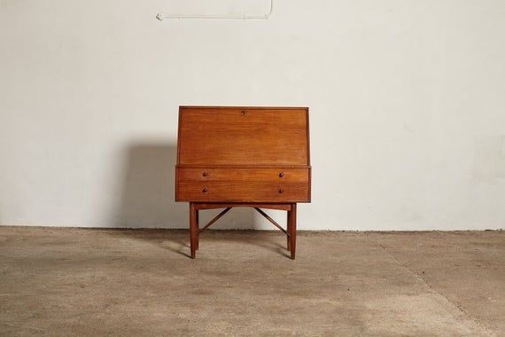 Very rare Ib Kofod Larsen Secretary Desk / Bureau, made by PA Pedersen, 1954, Denmark. Made of teak, with 2 drawers, a drop leaf, several smaller drawers and a drop down mirror inside. With one original key.H 115cm W 100cm D 50cm In good original vintage condition.   Some signs or use and wear consistent with age and use.   Minor veneer loss / professional repair to back corner edge (as seen in final photograph).  One small hole for a wire was made in the back panel.Ships worldwide.    Please co
