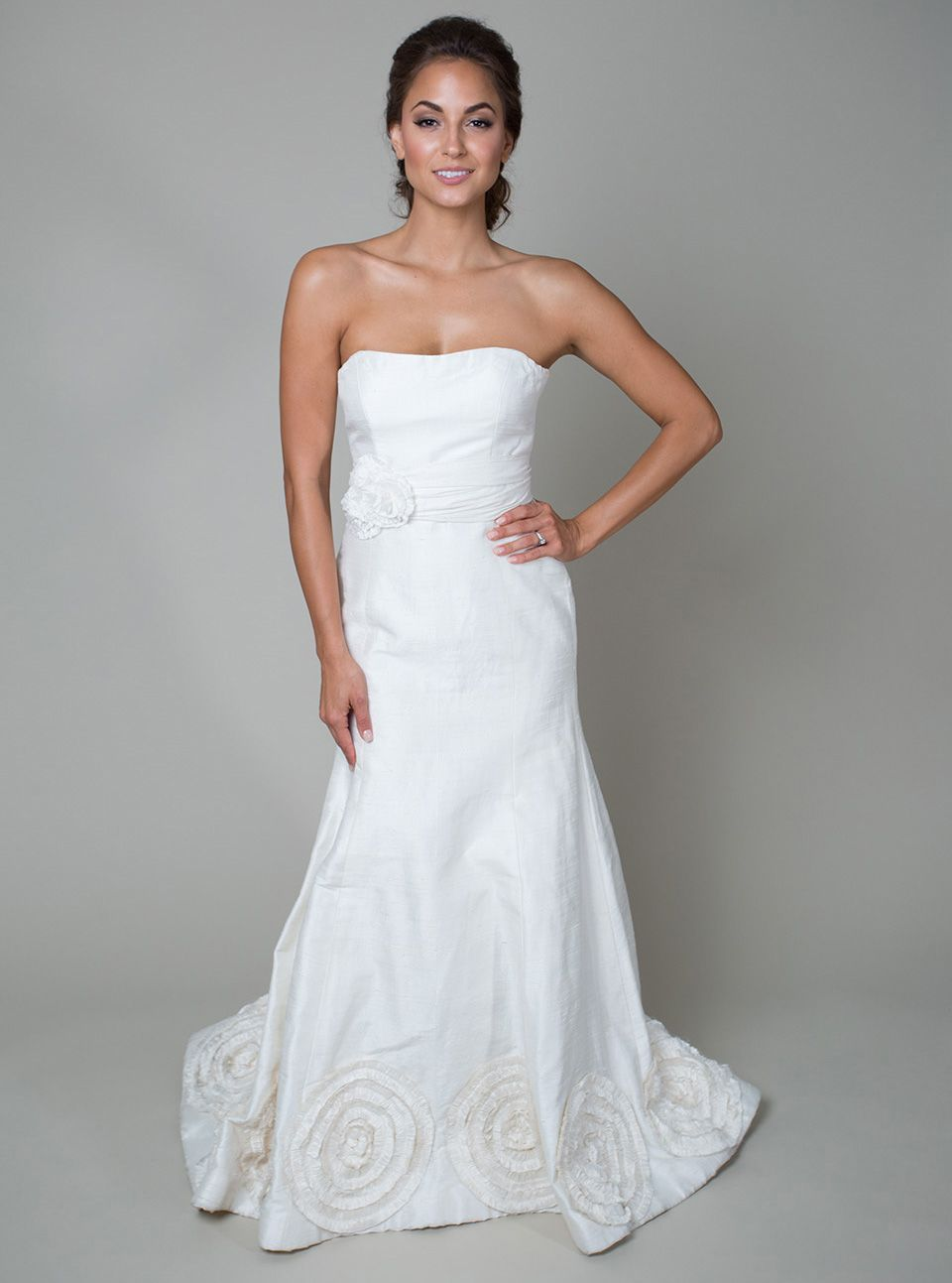 'Mary Cerella' Charming and nostalgic, this fit-to-flare gown features a straight neckline, chapel train, and hand-made flowers bordering the hem. The waist is defined with the Mary Cerella belt featuring a ruched waistband and hand-made flowers.