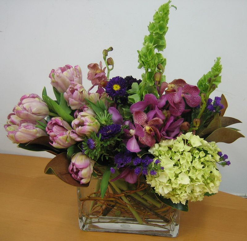 This Is A Cube Vase Floral Arrangement That Features Tulips Asters Mokara Orchids And Bells Of Ireland In Beautiful Floral Decor Flower Arrangements Floral