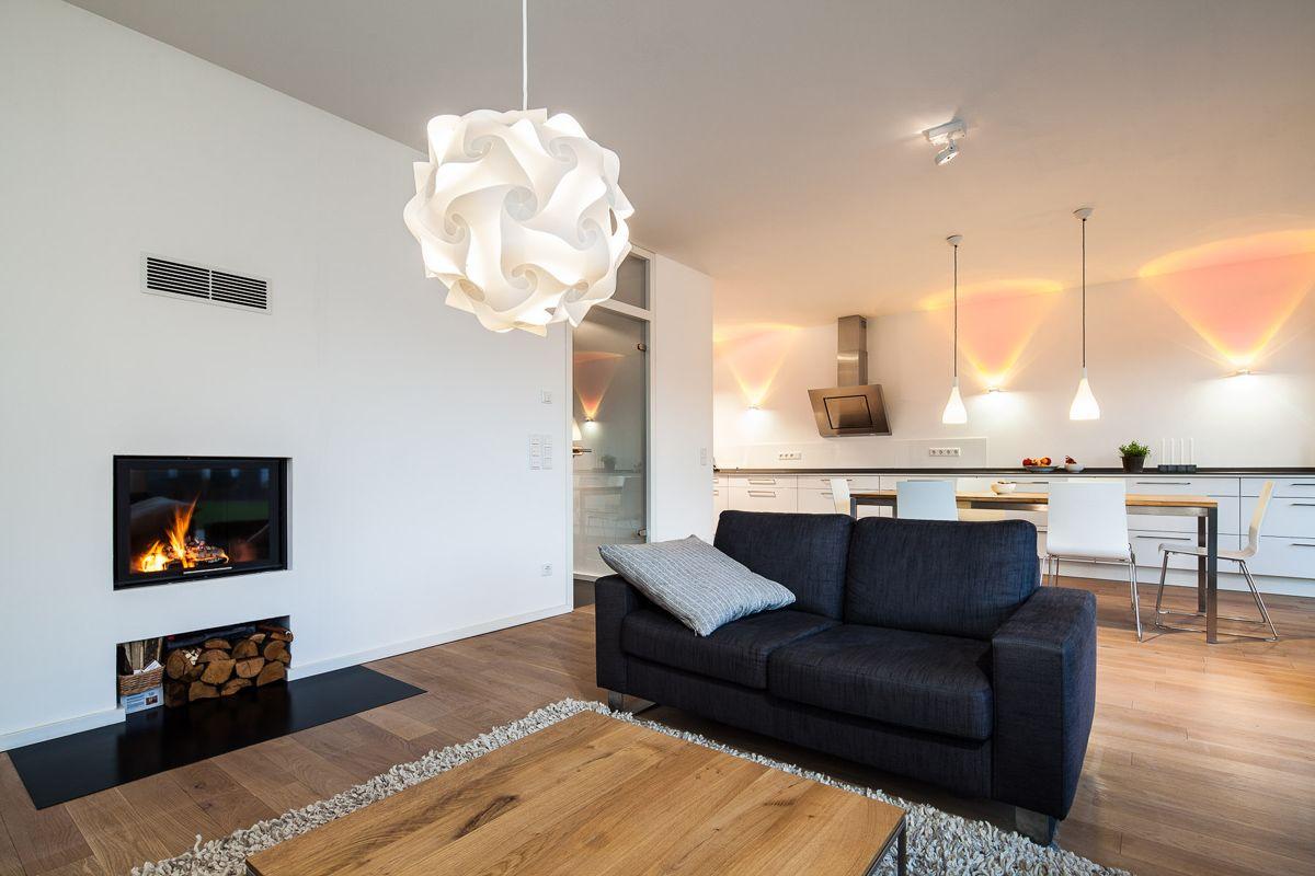 Haus L. - Wohnzimmer mit integriertem Kamin und Blick auf Essbereich ...