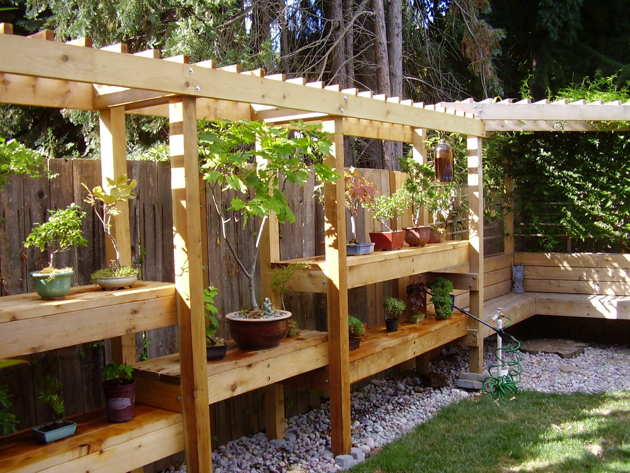 Love the combo of the pergola, bench seat and shelving incorporated ...