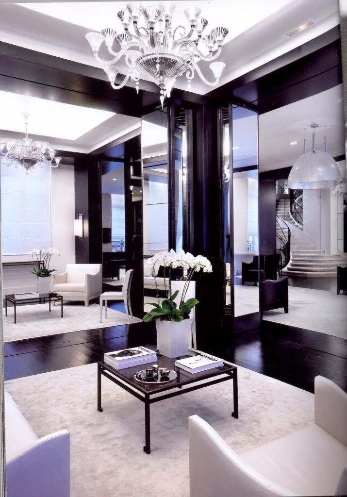 Modern Salon Gorgeous Dark Wood Flooring With Plush White Area Rugs, White  Leather Chairs, Mirrors, Chandeliers, And Winding Staircase.