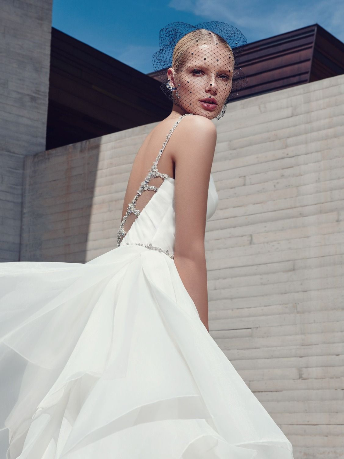 This glamorous ballgown features a pleated bodice and tiered layers of Marquice organza. Swarovski crystals and beading adorn the spaghetti straps, statement back detailing, and waistline. Finished with sweetheart neckline, crystal buttons and zipper closure.