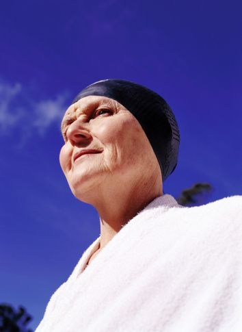 Stock Photo : Low angle view of an elderly woman wearing a bath robe and a swimming cap