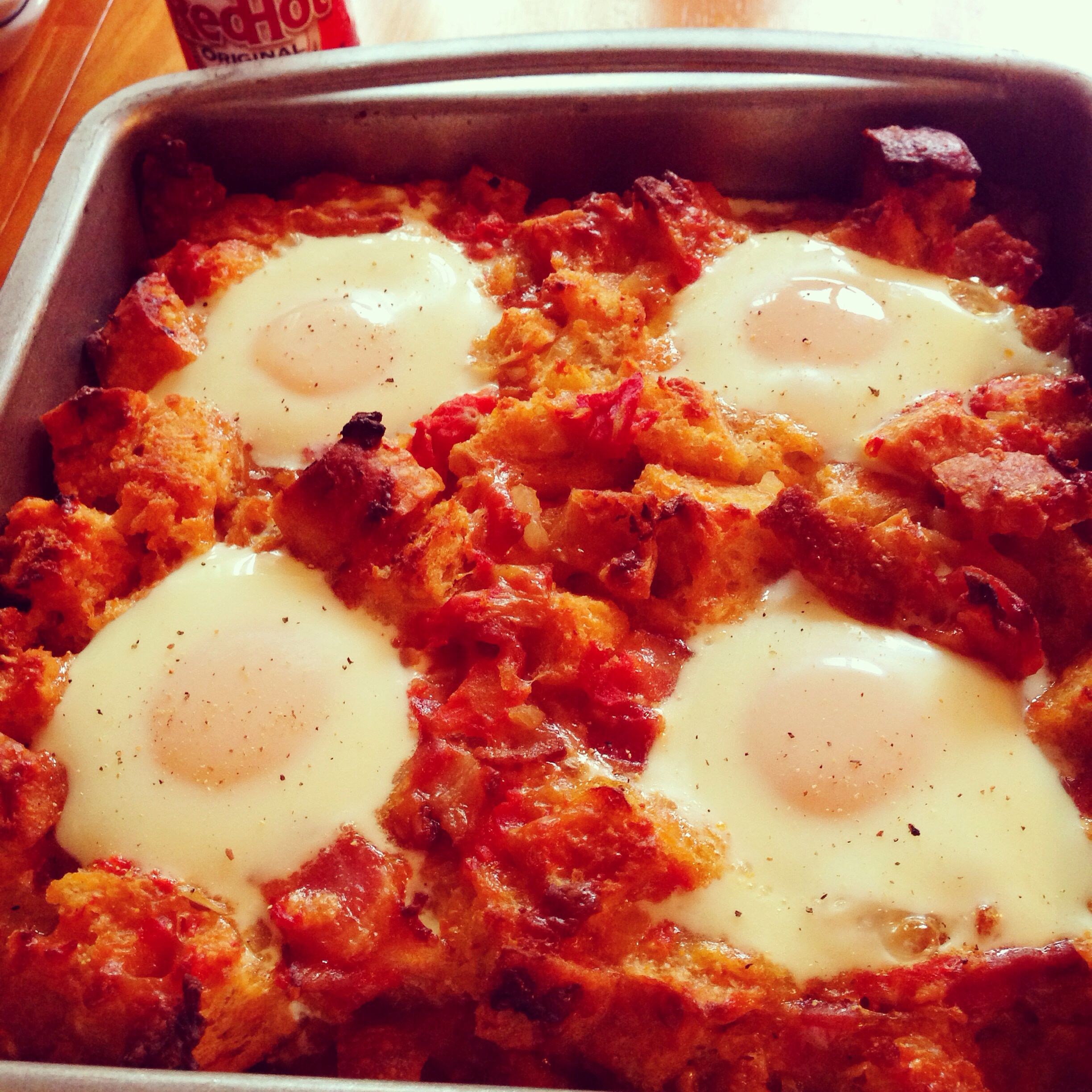 #breakfast bake with cubed sourdough bread, bacon, Monterey Jack and cheddar cheese, tomatoes topped with cracked egg