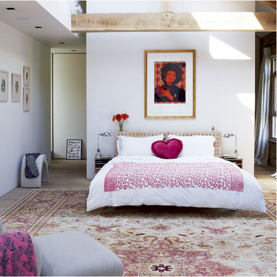 airy, spacious boho bedroom with raspberry accents, red flowers, huge oriental rug, heart pillow, raw wood beams