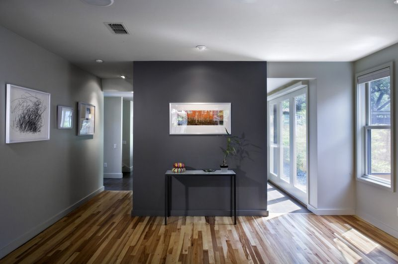 best gray paint colors for living room. charcoal grey accent wall  modern living room by Webber Studio Architects love the wood floor and dark unsure on painting