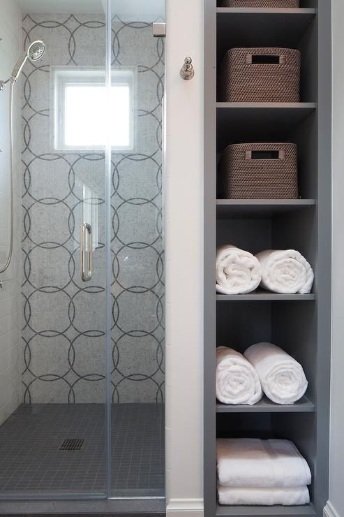 Gray Niche Shelves Stuffed With White Towel And Woven Baskets Are Positioned Beside A Walk In Shower Boasting Window In Shower Trendy Bathroom Bathroom Storage