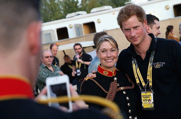 Prince Harry poses with military personnel backstage at the closing ceremony where the royal vowed to do more to find work for injured soldiers.