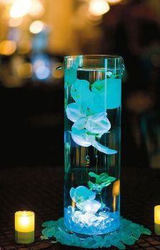 Need blue centerpieces for your blue wedding? Put petals in a vase and then use a waterproof colored LED light to illuminate them.