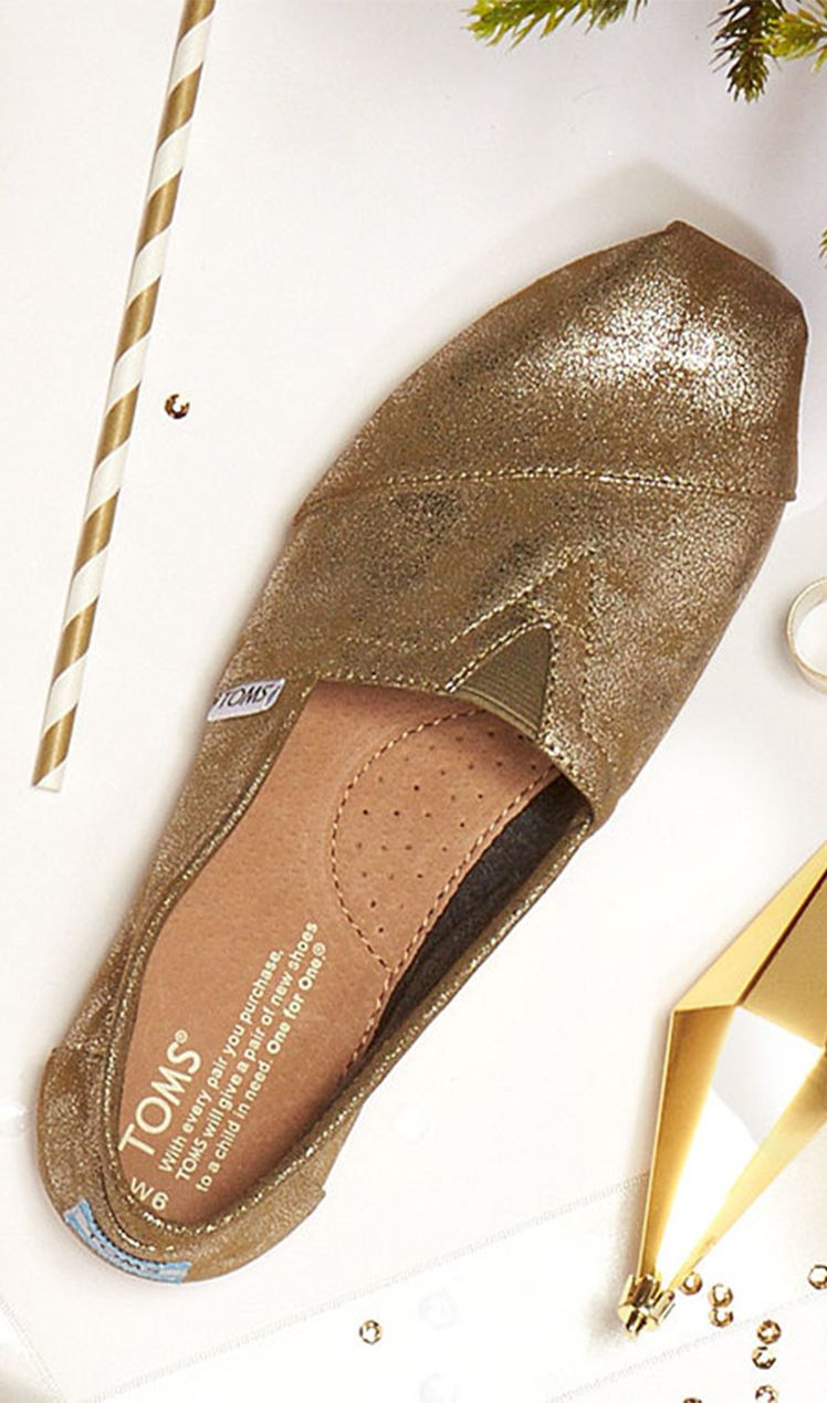 383272c15798 TOMS Metallic gold Classics are a wish list must have. Not only are these  slip-ons high on style, but each pair provides a pair of ...