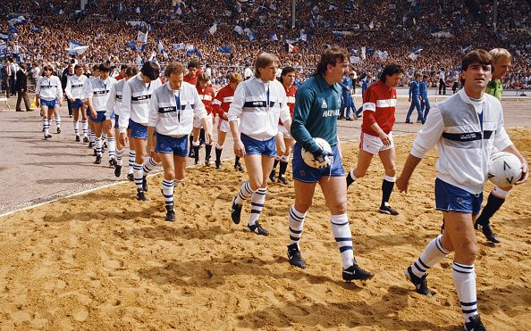 Everton captain Kevin Ratcliffe leads his Everton team out over the sand greyhound track onto the pitch before the 1985 FA Cup Final between Everton...