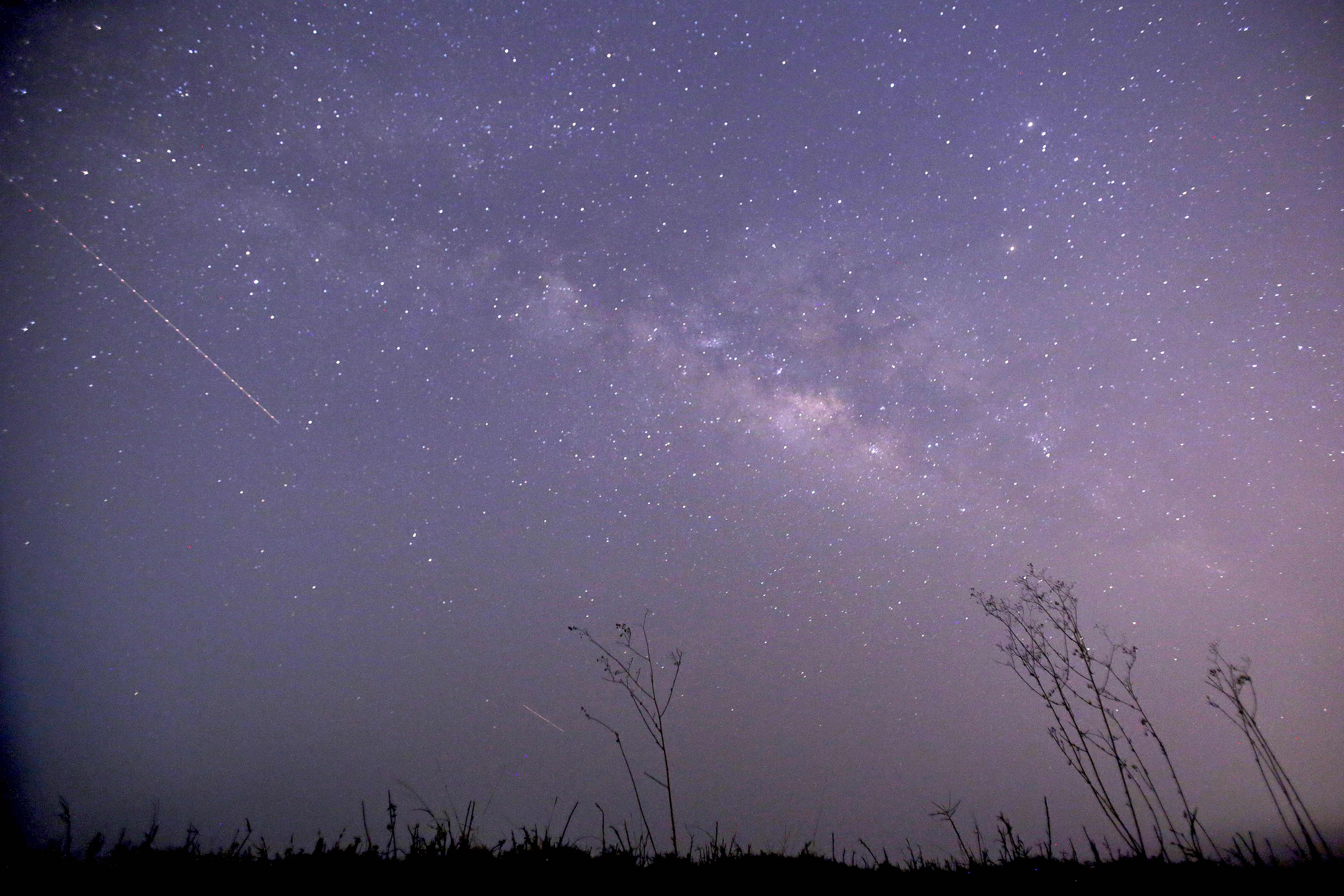 This long-exposure photograph taken on April 23, 2013 on Earth Day shows Lyrids meteors shower passing near the Milky Way in the clear night sky of Thanlyin, nearly 14miles away from Yangon. AFP PHOTO