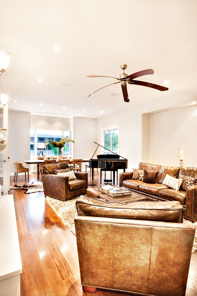 Living room with an AWESOME large ceiling fan! The brown blades perfectly complement the leather furnishings.