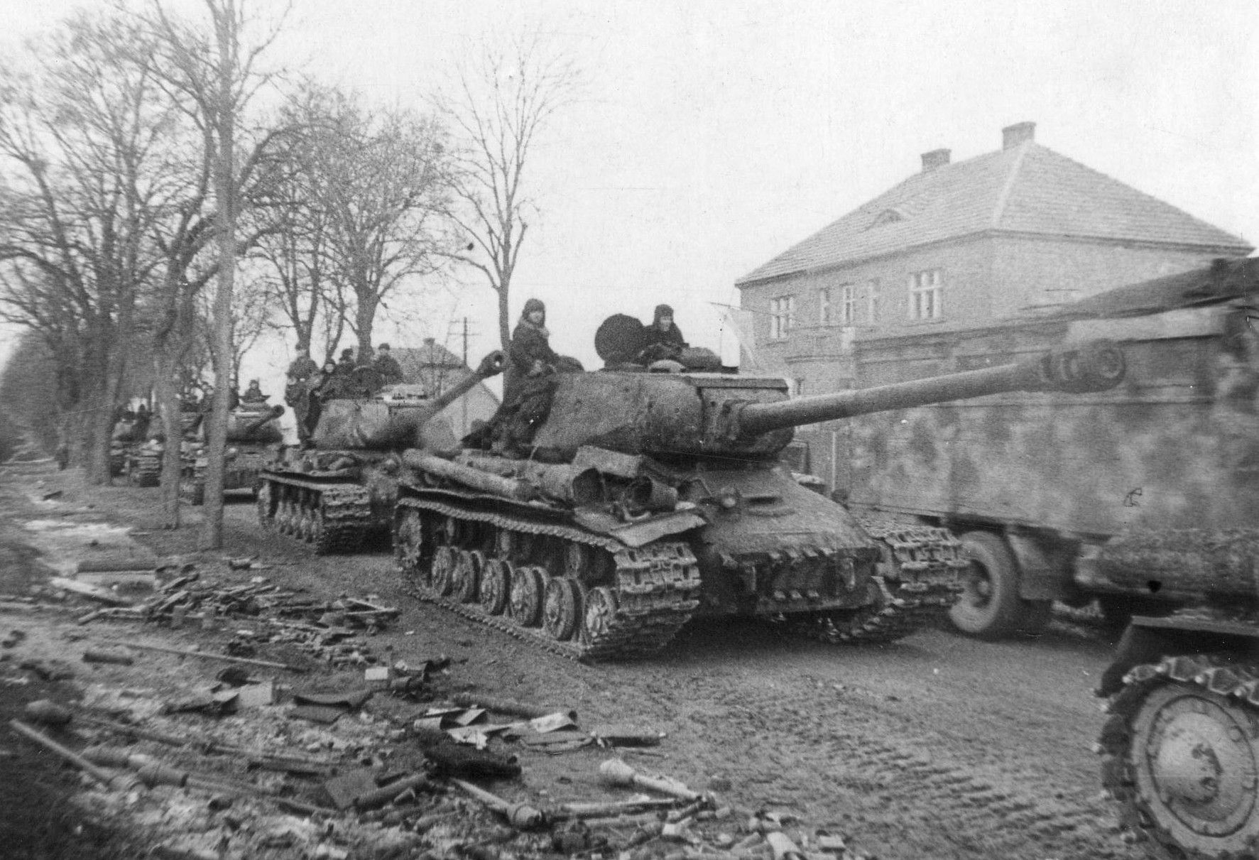 Heavy Soviet armor belonging to 1st Belorussian Front rolls into East Prussia, Feb 1945. Note the panerfaust (German bazooka) littering the side of the road.