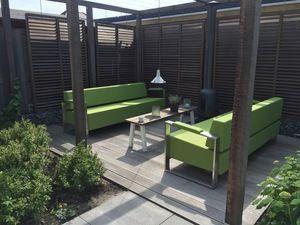Groene tuinmeubelen met rvs en allweather stof op houten vlonder