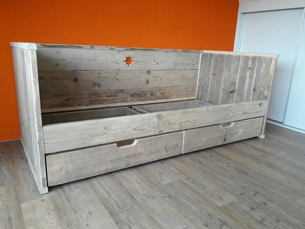 Bed gemaakt van zeer oude planken voorzien van lades die voorzien