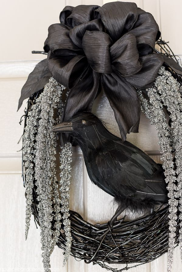 diy spooky glam halloween wreath with glittery stems draping down and a black crow to welcome your guests