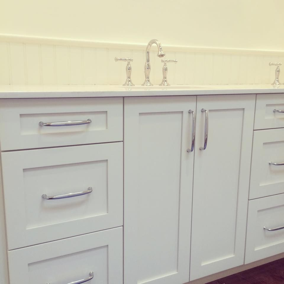 This white bathroom vanity features traditional shaker style designs ...