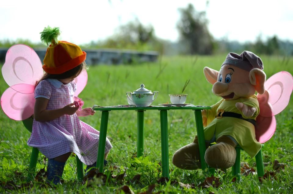 Adorable little butterfly fairy girl with her dopey friend enjoy a tea party and talk story.  Cute photo idea