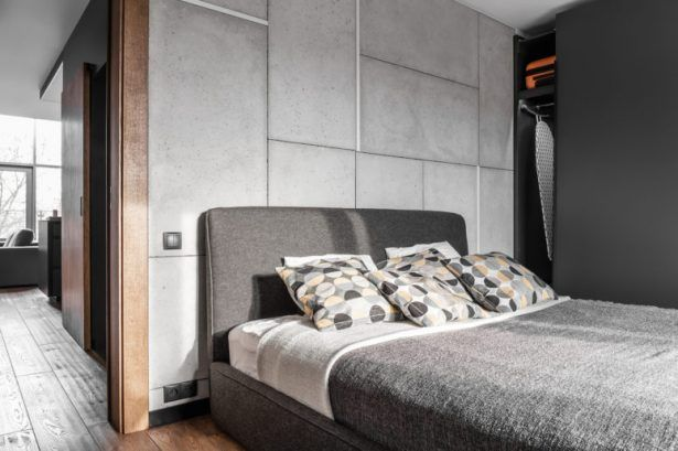 Apartment Large Grey Upholstered Bed With Patterned Pillows Near Grey  Concrete Panels And Matte Black Wardrobe