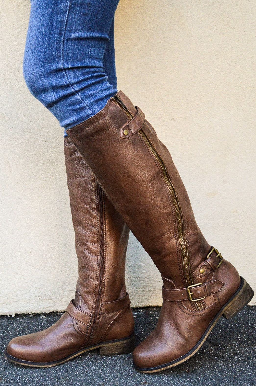 Product Details. This season, saddle up with sophisticated style and the new Karmin Riding Boot from Madden Girl! Rocking a tall riding boot silhouette, the Karmin Boot features synthetic leather uppers with a wraparound harness strap, decorative back zipper with open gore and buckle strap, and medial side zipper for easy slip-on and off.