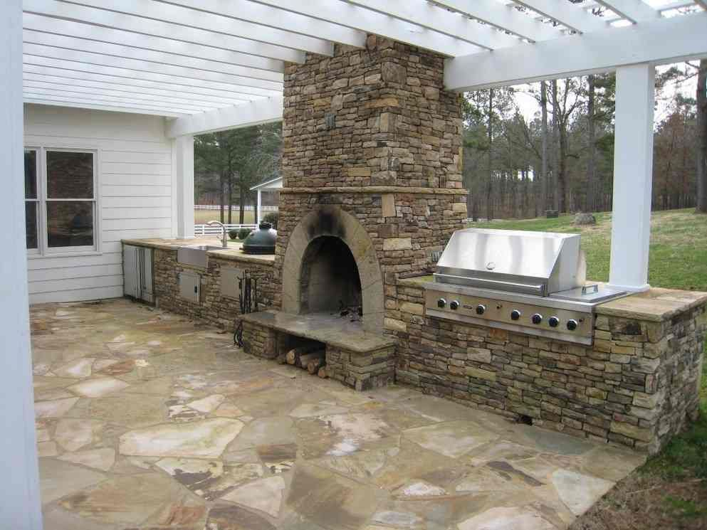 Outdoor kitchen with fireplace and attached to house pergola