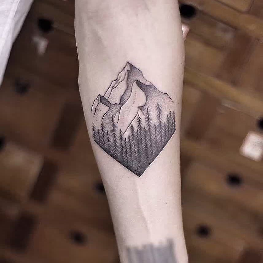 Mountains and trees tattoo by Aki Wong inked on the left
