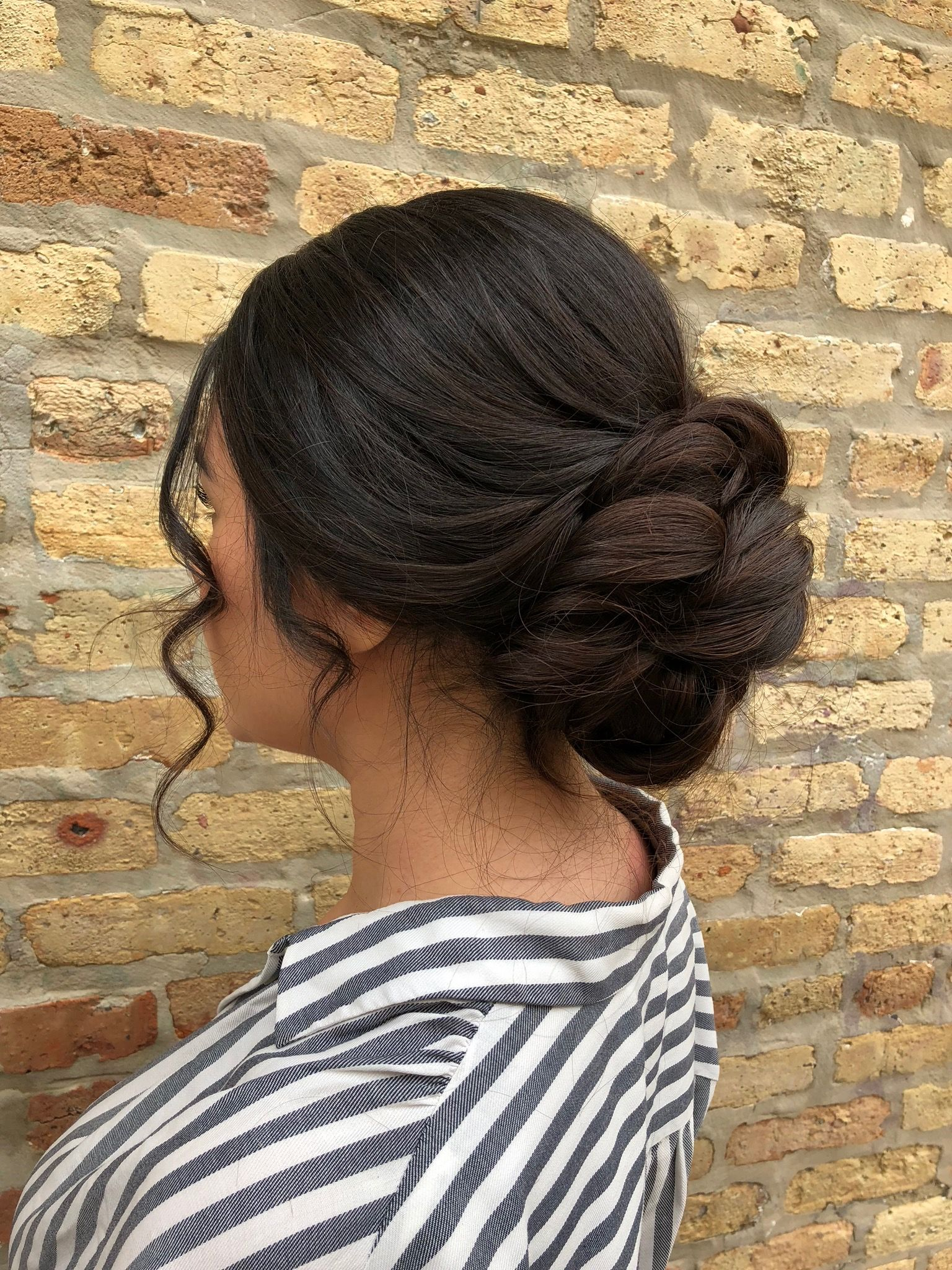 elegant swept back updo with low bun + curly face framing