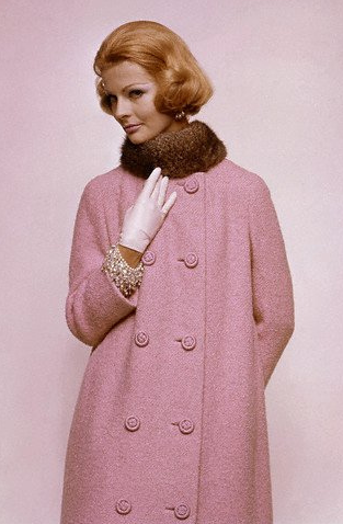 1960 Angela Howard in a collarless tweed coat in wool with cord buttons; opossum fur ruff by Georges Kaplan