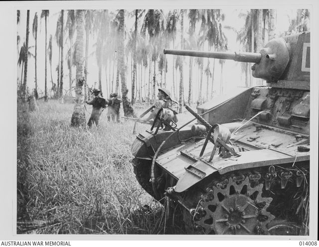 1943-01-07. PAPUA, GIROPA POINT. MEMBERS OF 2/12TH INFANTRY BATTALION ADVANCE AS GENERAL STUART M3 LIGHT TANKS MANNED BY B SQUADRON, 2/6TH ARMOURED REGIMENT, BLAST JAPANESE PILLBOXES IN THE FINAL ...