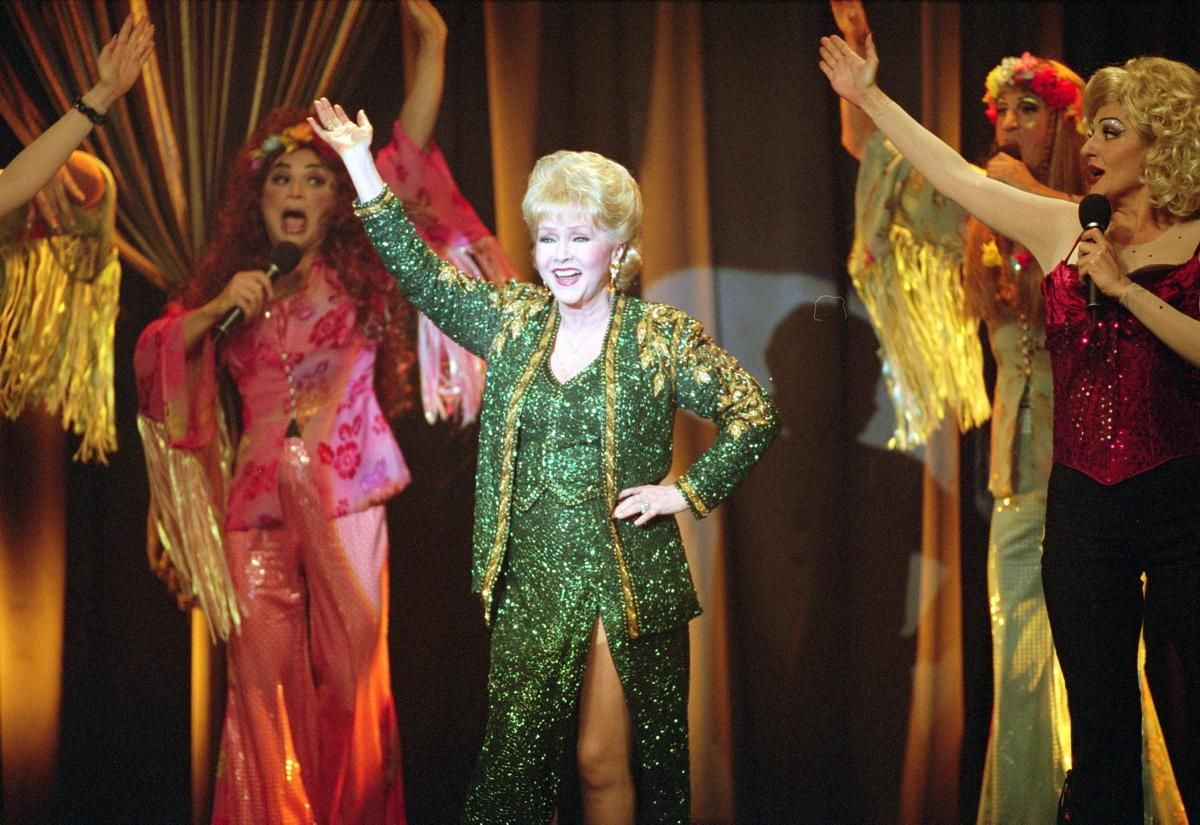 """After a few minor appearances in television movies and even a documentary, Reynolds was back in film, this time playing herself in the 2004 movie """"Connie and Carla."""" She's pictured here with """"the girls"""" on stage doing what she always did best!"""