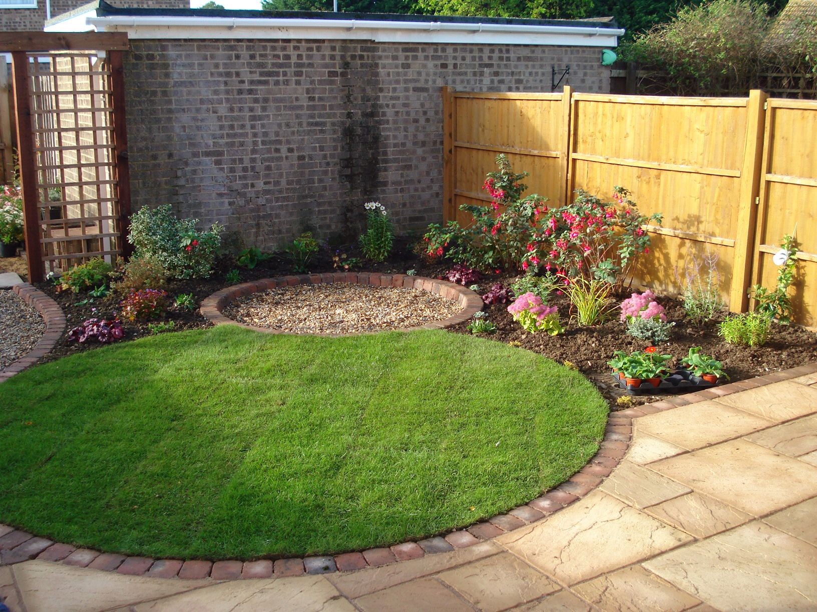 small circular lawn with tiny round patio beyond for a coherent effect in an urban garden